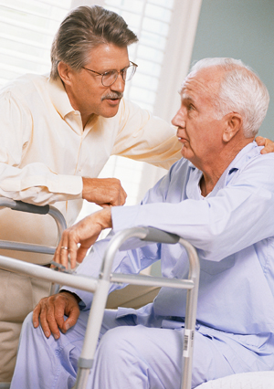 Man comforting older man with walker