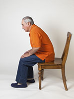 Man sitting at front edge of chair preparing to stand up.