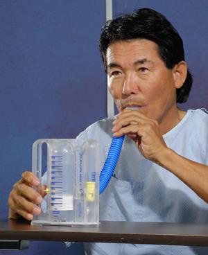 Man wearing hospital gown using spirometer.