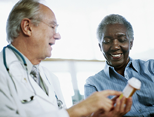 Doctor looking at pill bottle with patient.
