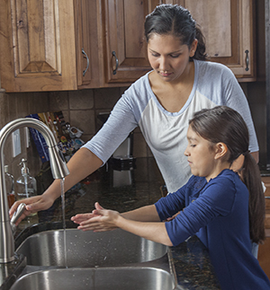 Woman helping girl wash hands in kitchen sink.