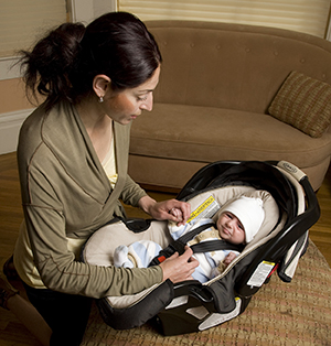Woman Securing Baby In Carrier