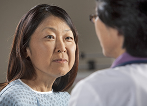 Woman wearing hospital gown listening to healthcare provider