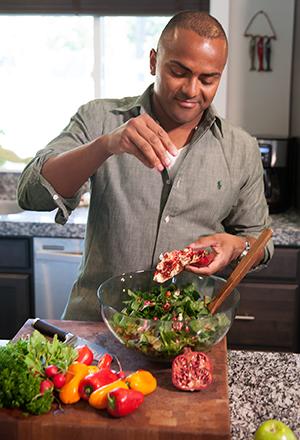 Man making salad in kitchen.