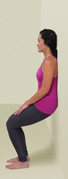 Woman standing with back against wall doing wall slide squat.
