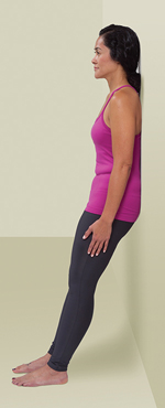 Woman standing with back against wall doing wall slide squat in starting position.