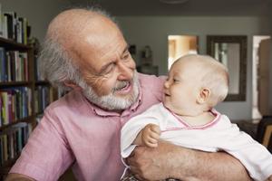 A senior man and baby boy smiling at home.