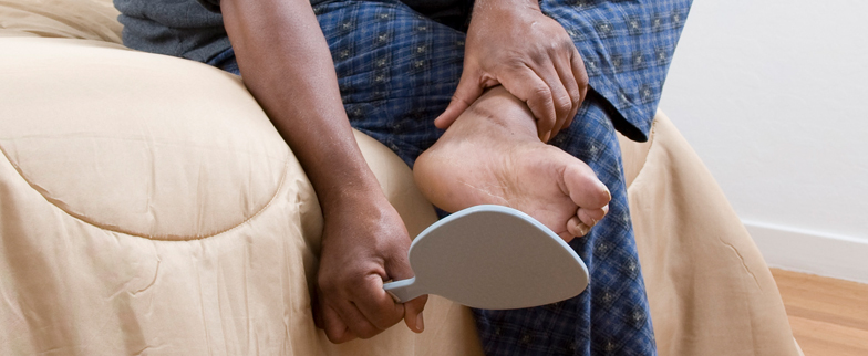 Cropped image of a man checking his feet with a hand mirror