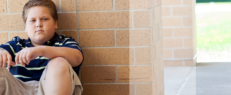 Young teenaged boy leaning against a brick wall