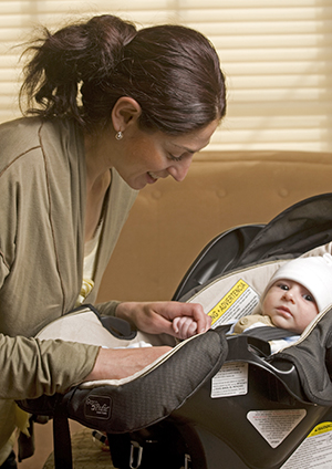 Woman securing baby in carrier.