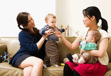 Dos mujeres sentadas en el sofá. Cada una sostiene a un bebé y juega con él.