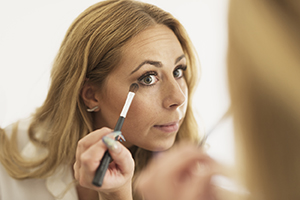 Woman looking in mirror, putting on eye makeup.
