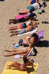 A number of people lying on towels on the beach