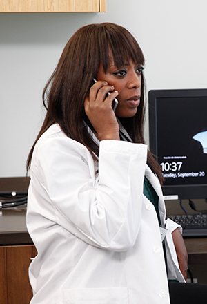 Healthcare provider talking on phone in exam room.