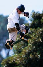 Picture of a young boy, in protective gear, skateboarding