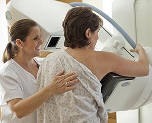 Technician helping woman during mammogram