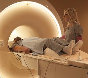 Technician preparing man for MRI scan.