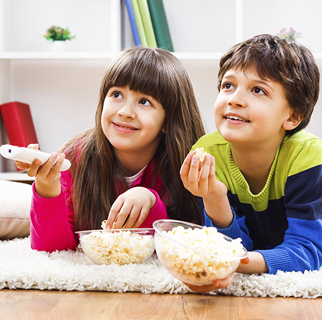 Two children eating popcorn while watching TV